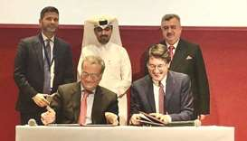 Italy's Giorgio Marrapodi and Unesco's Paolo Fontani sign the agreement in Doha as ambassador Salzan