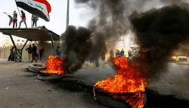 Iraq protesters burn tires to block a street during ongoing anti-government protests in Najaf