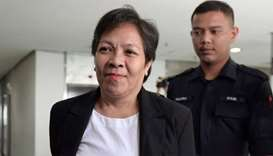 Maria Elvira Pinto Exposto, is escorted upon her arrival at the Shah Alam High Court