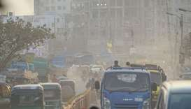 Motorists drive on a road under heavy smog conditions in Dhaka yesterday.