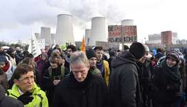 Climate activists hold placards during a demonstration in front of the Jaenschwalde power plant in e