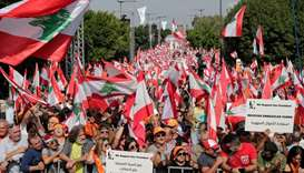 Supporters of Lebanese President Michel Aoun wave national flags and orange-coloured banners of the