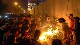 Iraqi demonstrators set tires ablaze behind the walls protecting the Iranian consulate in Karbala, s
