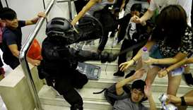 A riot police officer scuffles with protesters as he tries to detain a protester at a shopping mall