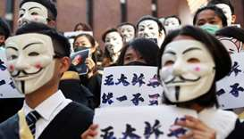 University students wearing Guy Fawkes masks pose during a news conference to support anti-governmen