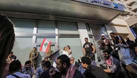 Members of the Lebanese Armed Forces stand guard as anti-government protesters shout slogans while a