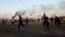 Demonstrators clash with members of Iraqi security forces during the ongoing anti-government protest