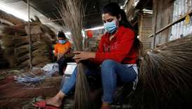 Workers make brooms at a workshop ahead of the Tihar festival, also known as Diwali, amid the spread