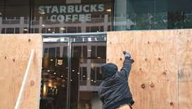 Wooden boards protect a Starbucks location near the White House in Washington, DC. Many Washington b