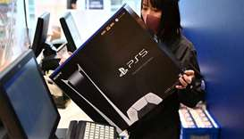 An employee prepares the new Sony PlayStation 5 gaming console for a customer on the first day of it