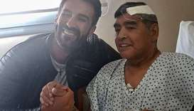 Argentine football legend Diego Maradona (R) shaking hands with his doctor Leopoldo Luque in Olivos,