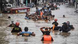 Rescuers pull a rubber boat carrying residents through a flooded street after Typhoon Vamco