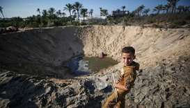A child stands near a ditch created after Israeli jets bombed an area in northern Gaza in Khan Yunis