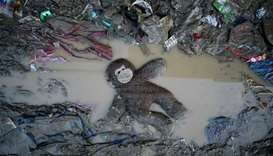A stuffed toy is seen in mud following the flood brought by a typhoon
