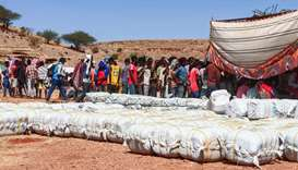 Ethiopian refugees fleeing fighting in Tigray province queue to receive supplies at the Um Rakuba ca