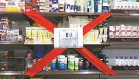 A boycott sign covers a store showcase displaying French products at a shop in Peshawar.