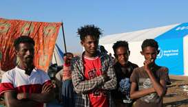 Ethiopians who fled the ongoing fighting in Tigray region, pose for a photograph as they wait to be
