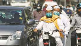 Men wear protective masks as they ride a motorcycle amid the outbreak of the coronavirus disease in