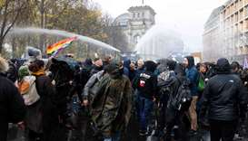 Police use a water cannon to disperse protesters demonstrating against measures imposed by the Germa