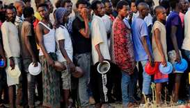 Ethiopian men who fled war in Tigray region, queue for wet food ration at the Um-Rakoba camp, on the