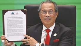 "Malaysia's Prime Minister Muhyiddin Yassin holds up a copy of the ""Apec Putrajaya Vision 2040"" docum"