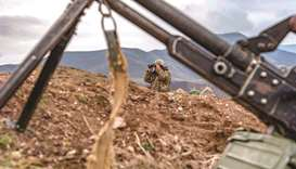 An Armenian soldier looks through binoculars during a patrol yesterday at the checkpoint nearby a de