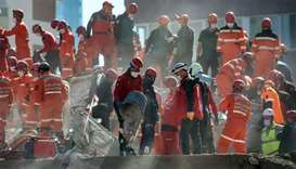 Rescuers are at work during the ongoing search operation at the site of a collapsed building as they