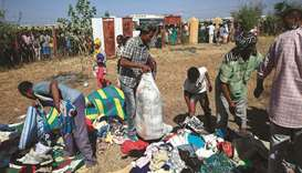 Ethiopian refugees who fled fighting in the Tigray Region receive clothing aid at the Village 8 bord