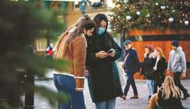 Pedestrians wearing protective face covering to combat the spread of the coronavirus, look at a phon