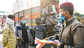 A Delhi Civil Defence (DCD) volunteer fines a truck owner for not maintaining social distancing in t