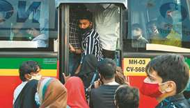 Passengers try to board a crowded bus in Mumbai yesterday.