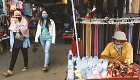 Women wearing protective masks walk as a drinks vendor sits waiting for the customers at Tanah Abang