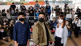 Pro-democracy activists Ivan Lam, Joshua Wong and Agnes Chow arrive at the West Kowloon Magistrates'