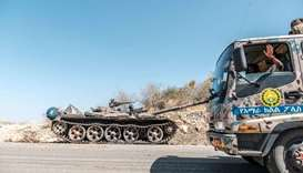 A damaged tank stands abandoned on a road as a truck of the Amhara Special Forces passes by near Hum