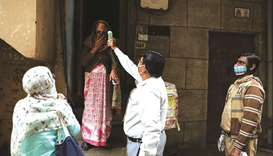 A health worker wearing a protective face mask checks the temperature of a woman while 