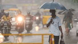 A man walks under an umbrella during heavy rains as cyclone Nivar approaches the eastern coast, in C