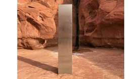 The shiny, triangular pillar -- which protrudes approximately 12 feet from the red rocks of southern