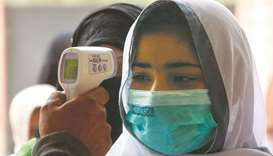 A school official checks the body temperature of a student wearing face mask as she enters a school