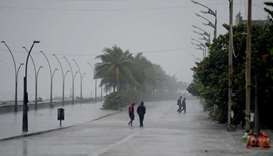 Policemen walk along a deserted beach road during heavy rains as cyclone Nivar approaches the southe