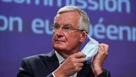 EU's Brexit negotiator Michel Barnier takes off his face mask as he holds a news conference after a
