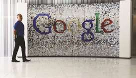 An employee stands next to a sign featuring Google logo inside their UK headquarters at Six St Pancr
