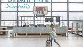 A traveller pushes a suitcase past a closed cafe near the check-in desks at London Gatwick Airport i