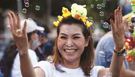 A protester wears toy ducks on her head during a pro-democracy rally demanding the prime minister to