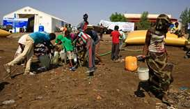 Ethiopian refugees who have fled the Tigray conflict, fill bottles and containers with water after a