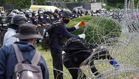 Protesters try to remove barb wires ahead of a pro-democracy rally demanding the prime minister to r