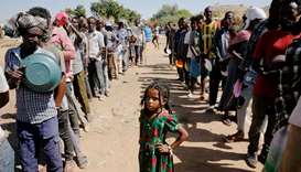 Ethiopian refugees wait in lines for a meal at the Um Rakuba refugee camp which houses Ethiopian ref