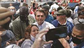 President Bolsonaro poses for a 'selfie' with a supporter after voting yesterday during the second r
