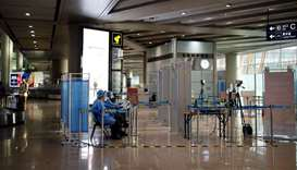 Staff members in protective suits sit at a checkpoint at Beijing Capital International Airport, in B