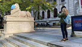 "A woman takes a photo of the he ""Patience and Fortitude"" marble lion, wearing a mask, at the New Yor"