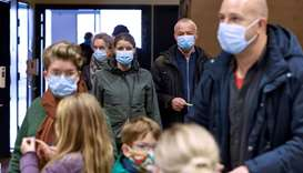 People wearing face masks cue to be tested for coronavirus COVID-19 during a mass testing in the Are